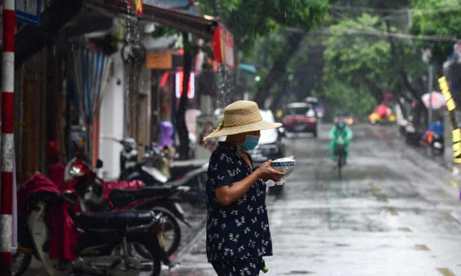 A woman carries a bowl of pho across the street in the rain in Hanoi