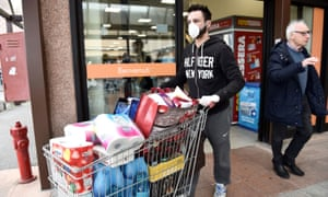 A man wearing a face mask pushes a cart at a supermarket in the town of Casalpusterlengo, which has been closed by the Italian government due to a coronavirus outbreak in northern Italy.