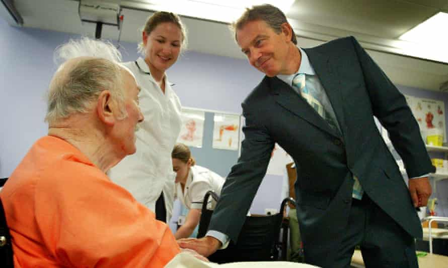 Tony Blair shaking the hand of a hospital patient.