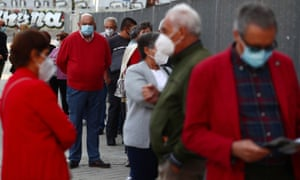 People wait in a queue outside a cultural centre before a coronavirus antigen test in Madrid