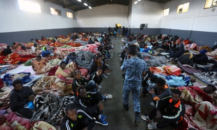 Migrants sit in a shelter at a detention centre on the outskirts of the Libyan capital, Tripoli.