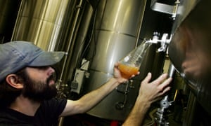 A Lagunitas brewer takes a sample of beer from a tank at the brewery n Petaluma, California.