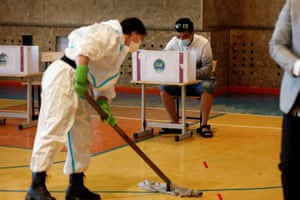 A worker wearing a protective suit mops the floor near a man casting his vote in Ulaanbaatar.