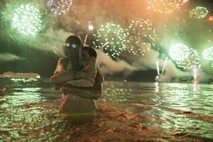A couple hug as fireworks explode over Copacabana beach in Rio de Janeiro during the New Year's celebrations.