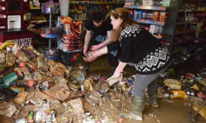 Shop workers clear rubbish from a store in Cockermouth