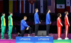 Gold medalist Race Imboden of United States takes a knee during the national anthem ceremony for fencing at the Pan American Games in 2019