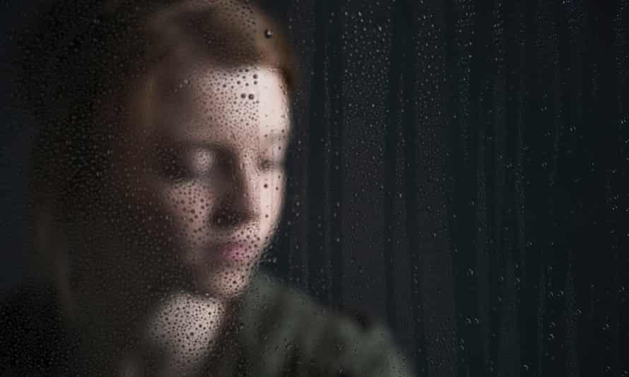 Teenager behind a window with raindrops