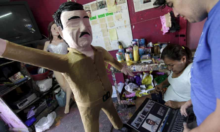 Workers refer to images on a laptop in front a pinata depicting drug lord Joaquin 'El Chapo' Guzmán at a workshop in Mexico last month.