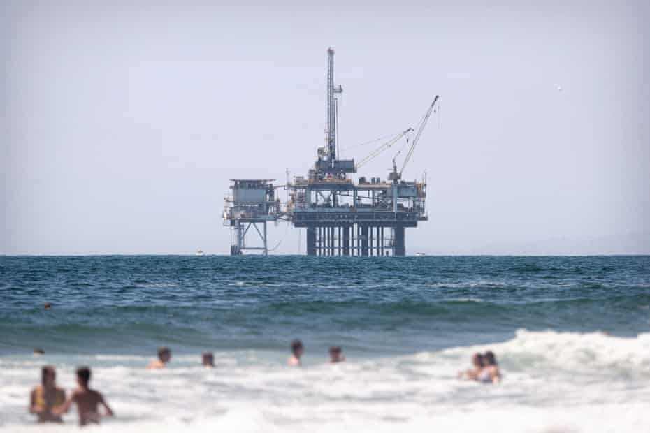 People swim in the Pacific Ocean next to the Huntington beach pier in front of an offshore oil rig in Huntington Beach, California.