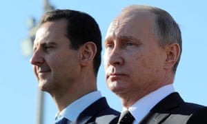 Assad and Putin watch troops marching at the Khmeimim air base in December last year. For Putin, helping the regime is an all-or-nothing proposition.