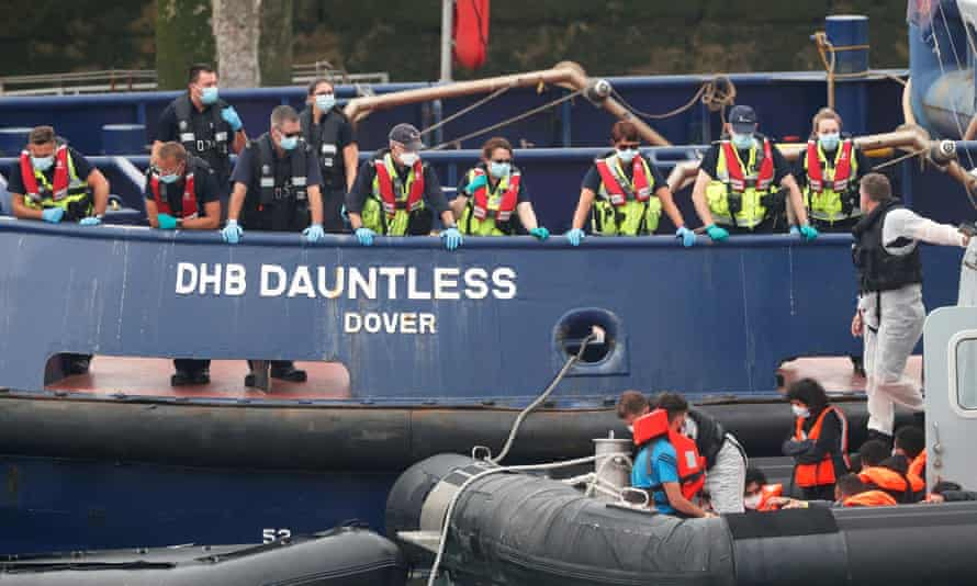 UK officials watching as migrants are brought into Dover harbour.