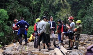The British ambassador to Vietnam, Giles Lever, (centre, with blue jacket) talks to local officials as he tours the site where three British tourists were killed