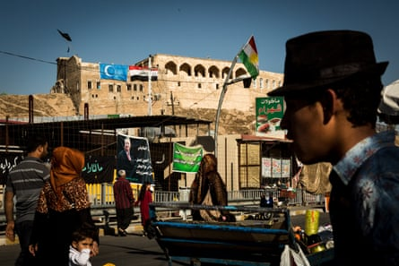 Civilians walk past Iraqi and Turkmen flags hanging from the side of the Citadel in the centre of Kirkuk.