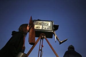 A woman looks through the viewfinder of the old wooden box camera used by Maldonado