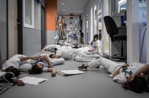 Nursing and care personnel lie on the floor during a demonstration on International Nursing and Care Day at the Mont Legia hospital in Liege, Belgium