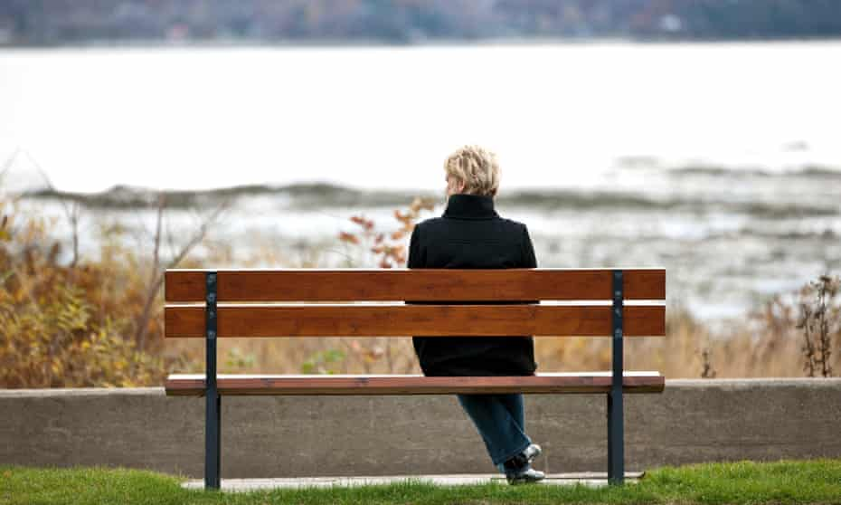 Woman sitting alone on park bench.