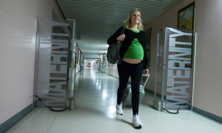 Heavily pregnant lady walking towards maternity ward in a hospital pulling luggage.