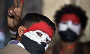 Egyptian youths with their faces painted in the colours of the national flag