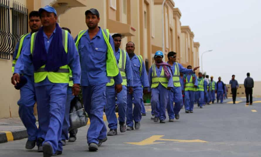 Foreign labourers walk back to their compound.