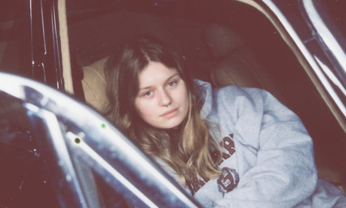 Photograph of girl in red, a white teenager girl with long dirty blond hair and a septum piercing. She's wearing a Harvard sweatshirt and lying down in the passenger seat of a car, looking at the camera.