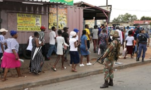 A member of the South African national defence force keeps watch as shoppers leave the Shoprite grocery store
