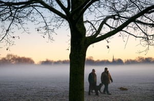 Two men walk their dogs through early morning fog on Clapham common