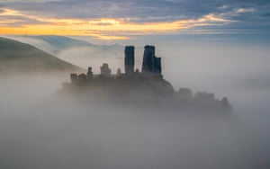 Dorset, UK: The sun rises behind the mist-covered Corfe Castle.