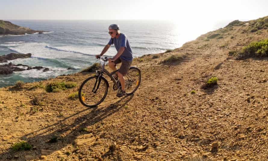 Portugal, Senior man mountain biking at the sea, Alentejo