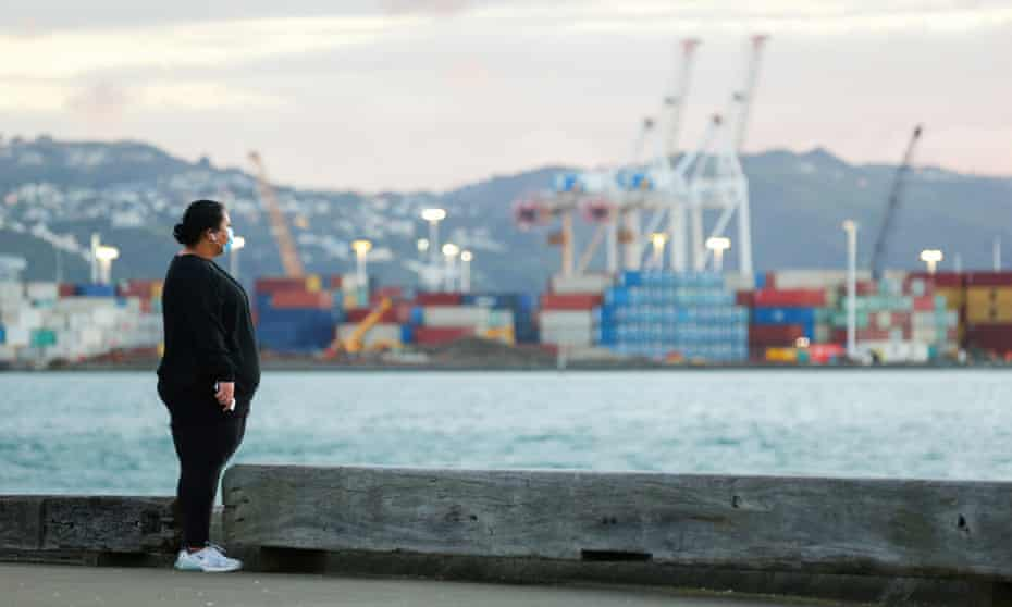 A pedestrian wearing a face mask looks out over Wellington Harbour, New Zealand.