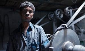 A boy poses next to heavy machinery in an aluminium pot factory in Dhaka, Bangladesh.