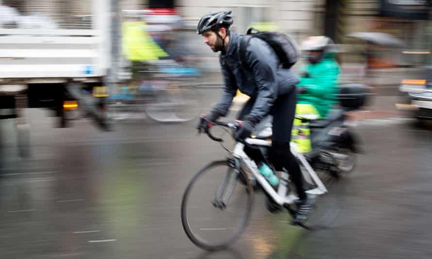 A helmeted cyclist on the streets of London.