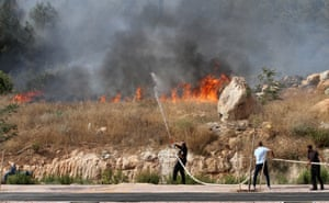 Modi'in, Israel: People try to put out a fire during a heatwave in which temperatures soared to more than 40C