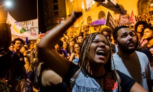 A woman shouts slogans during a protest against the Brazilian government following the fire.