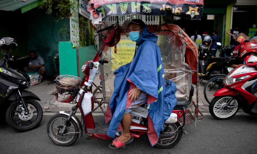 A rickshaw driver wears a makeshift protective Covid-19 suit and mask as he waits for passengers in Manila, Philippines.