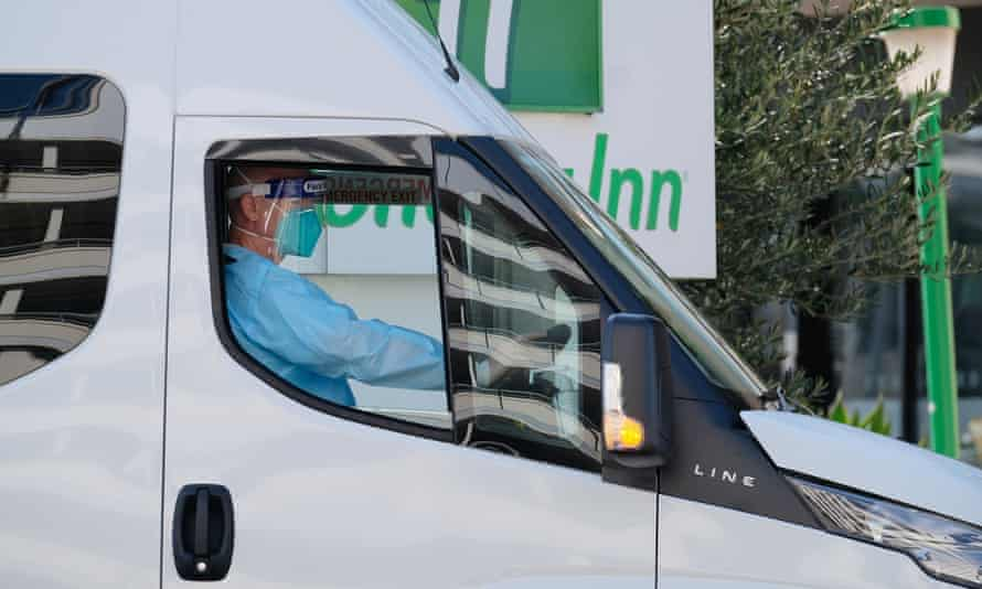 A driver relocates quarantining hotel guests at the Holiday Inn near Melbourne airport after an outbreak of the UK variant of Covid at the hotel.