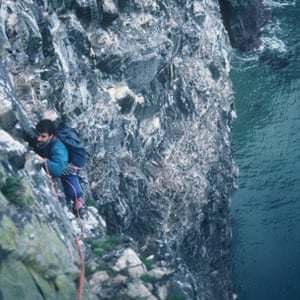 Climber on the cliff face high above the sea