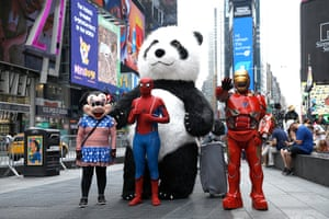 People dressed as cartoon characters pose in Times Square