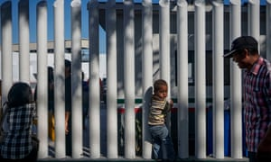 A young migrant from Honduras waits in line with his parents at the Mexico-United States border in Tijuana, Mexico. US President Donald Trump's fitful crackdown on immigration is gaining traction.