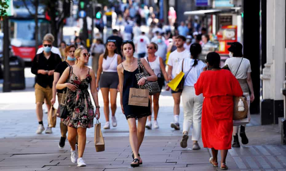 Shoppers on Oxford Street in London, some in masks, with the sun shining