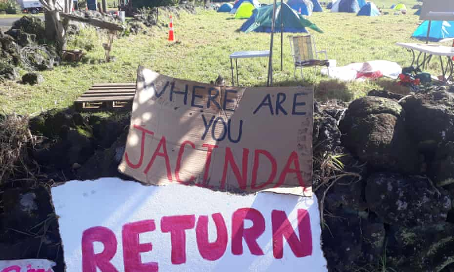 Protest signs at Ihumātao call for the New Zealand prime minister, Jacinda Arden, to visit. She has refused to intervene to stop proposed development.