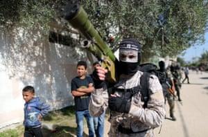 A militant holds guns in Khan Yunis, Gaza Strip