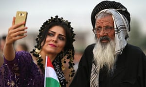 An Iranian Kurdish woman takes a selfie with a man at a gathering near Erbil to urge people to vote in the referendum.