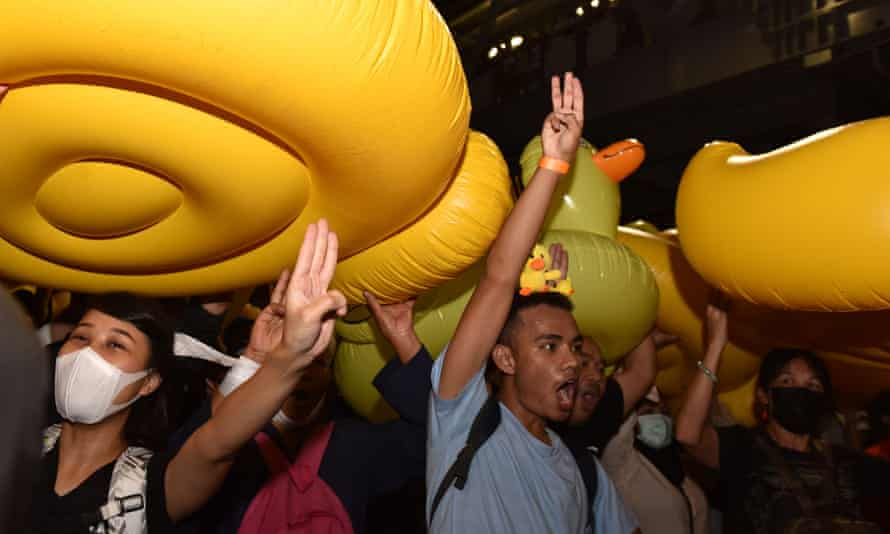 Protesters in Bangkok pass giant inflatable yellow ducks, a symbols of resistance, in the latest demonstration against Thailand's government and monarchy.