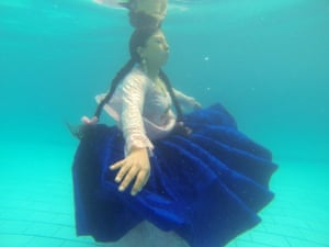 A woman in traditional Bolivian clothing submerged in water