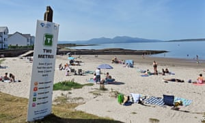 A sign at Ganavan Sands in Oban urges people still to take precautions and observe social distancing as they enjoy the beach on what was the hottest day of the year in parts of Scotland.