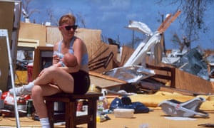 A woman feeds a baby outside the wreckage of a house following Hurricane Andrew in Florida, 1992.