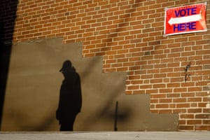 The early morning sun casts a voter's shadow against a wall when he arrives at a polling station in Aliquippa, Pennsylvania, USA.