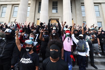 Demonstrators raise their fists as they gather on the steps of the Louisville Metro Hall on Thursday.