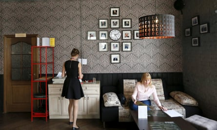 A customer sits in the President Cafe in Krasnoyarsk, where dozens of photos of Putin hang on the walls.
