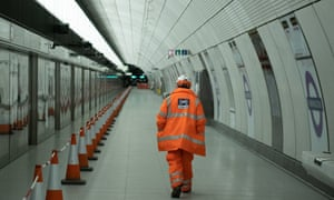 A member of the construction team walks past a sign on the platform of Farringdon Crossrail station